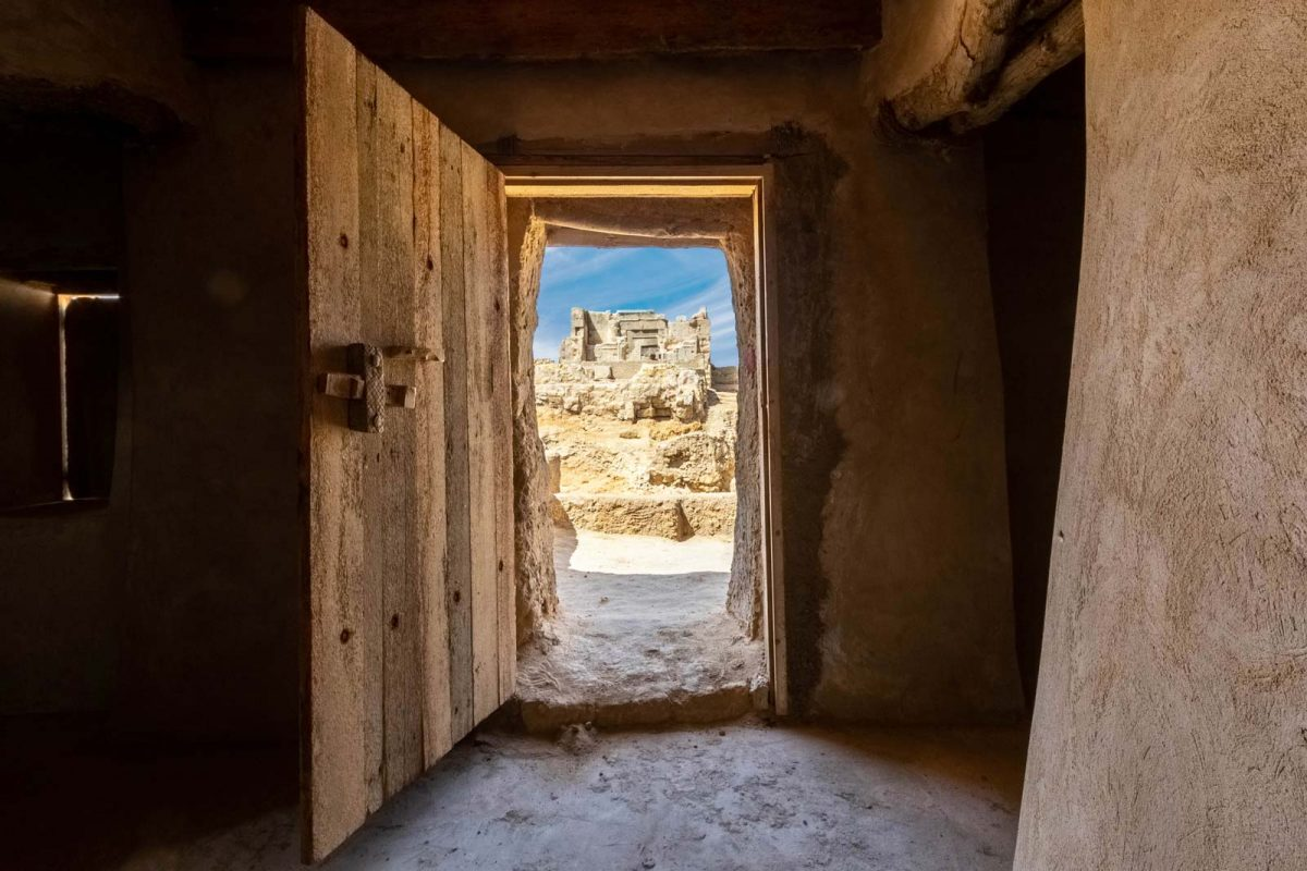 Temple of Amun through the doors of a mosque in Siwa, Egypt