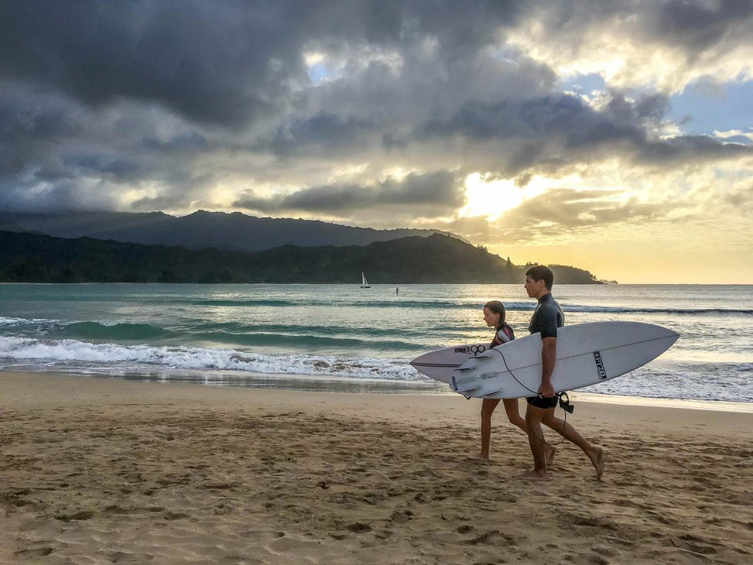 Surfers walking at sunset in Kauai, Hawaii