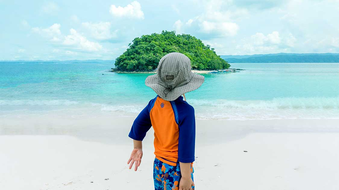 Young boy looking out at an island in the Philippines
